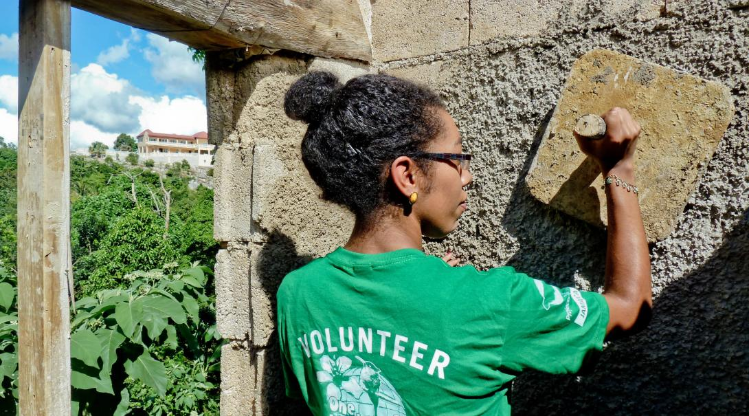 On a volunteer trip to Jamaica, a spring break volunteer plasters a wall.